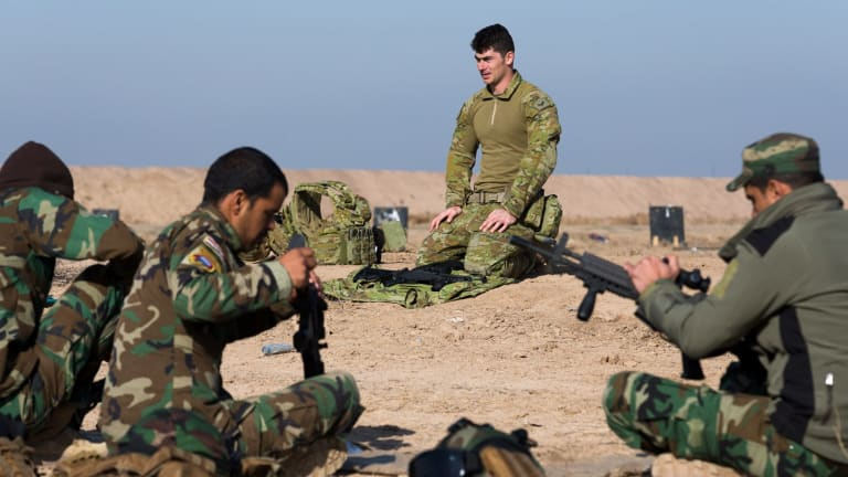Australian Army soldier Corporal Emmette Taylor, from Task Group Taji 4, teaches Iraqi Security Forces personnel how to strip a K-2 assault rifle in Iraq.