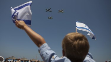 Israelis watch an air show during Independence Day celebrations in Tel Aviv.
