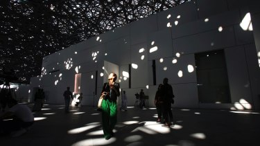 A journalist walks under the lights coming through of the dome at the Louvre Abu Dhabi, UAE, before its Saturday grand opening to the public.