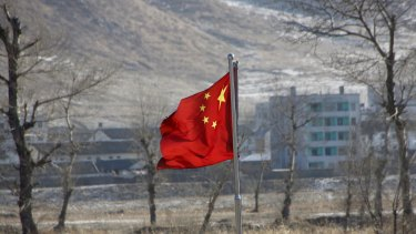 China's national flag flutters on the Chinese side of the banks of the Tumen river, as a North Korean village is seen behind.