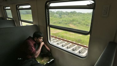 An ethnic Sinhalese Sri Lankan man eats his lunch during a train ride. For the hundreds of thousands of minority ethnic Tamils, the Sri Lankan government's repeated promises of post-war reconciliation ring false.