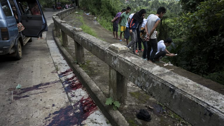 """Blood stains the roadside as  civilians view bodies dumped in a ditch by militants. The eight executed men, who were hogtied, had a cardboard sign tied to their bodies bearing the word """"munafik"""", or hypocrite."""