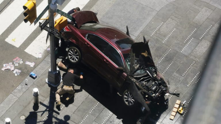 A police officer inspects the car crash scene at Times Square.