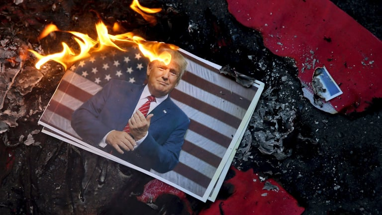 A portrait of Donald Trump is set on fire last month by Iranian protesting his decision to recognise Jerusalem as capital of Israel.