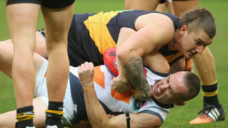 In close: Tom Scully is tackled by Dustin Martin during the tight encounter.