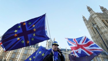 An anti Brexit demonstrator waves EU and British flags in Westminster in London on Friday.