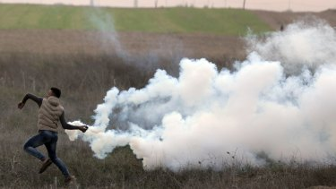 A Palestinian protester throws back a teargas canister fired by Israeli troops during clashes on the Israeli border with Gaza, on Sunday