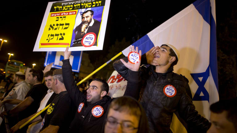 Right-wing Israelis demonstrate at the site of Wednesday's attack by a Palestinian motorist in Jerusalem. The placard shows Rabbi Meir Kahane, a hero to some on Israel's far right.