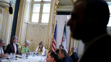 An Iranian security guard stands as US Secretary of State John Kerry (second from right) meets with the Iranian delegation including Iranian Foreign Minister Mohammad Javad Zarif in Vienna.