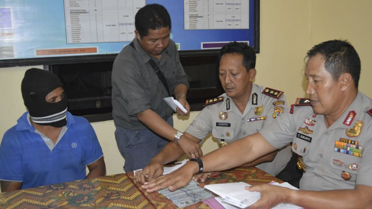 From left, seated: Captain Yohanis Humiang with head of the people-smuggling division of Nusa Tenggara Timur, Ibrahim, and Rote police chief Hidayat in June.