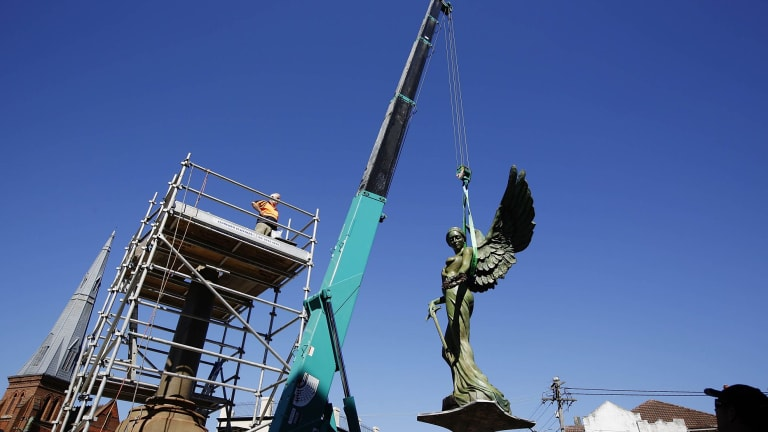 The Winged Victory statue is hoisted by a crane on to her final resting place in front of the Marrickville Town Hall.