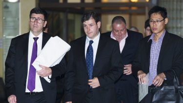 James Ian Longworth, second from left, leaves the Downing Centre District Court.