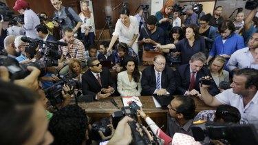 Members of the media surround Canadian Al-Jazeera English journalist Mohammed Fahmy, left, his  lawyer Amal Clooney, center, Canadian ambassador to Egypt, Troy Lulashnyk.