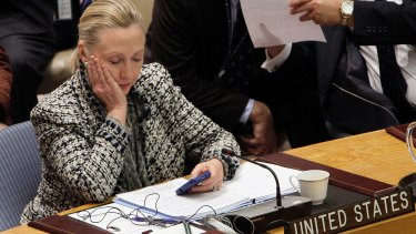 Then-Secretary of State Hillary Clinton checks her mobile phone after her address to the Security Council at the UN headquarters.