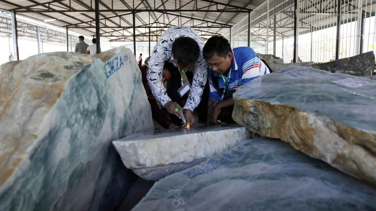 Merchants inspect jade displayed at the Gems Emporium in Naypyitaw earlier this month.