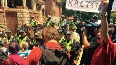 Police hold back anti-racist protesters at Parliament House.
