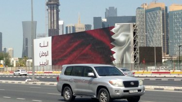 """An SUV drives past a billboard featuring the Qatari flag and the slogan """"God, Nation, Emir"""" in Doha."""
