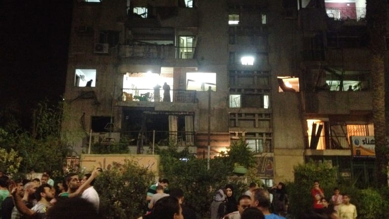 People look into and out of a building damaged by a bomb that exploded early on Thursday in Cairo.