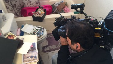 Journalists film inside the flat of Syed Farook and Tashfeen Malik in Redlands, California.