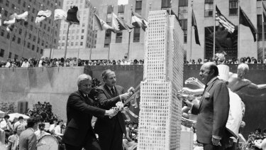 Rockefeller, second left, assists in slicing up a culinary replica of the Rockefeller Centre in New York on the building's 50th birthday in 1982.