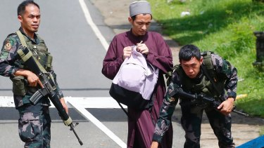 Government troops frisk a Muslim man at a checkpoint leading to Marawi city three days after Muslim militants lay siege in the city in southern Philippines.