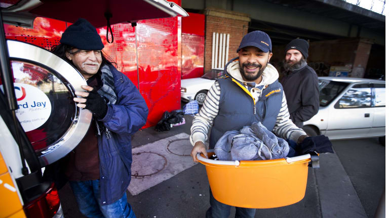 Tony Bautista (left) and Michael Jager (middle) make use of mobile van Orange Sky Laundry as Steve Cook (right) looks on. Orange Sky Laundry's founders have been nominated for Australia Day Awards.