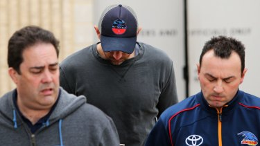 James Podsiadly (centre) leaves the Crows club rooms.