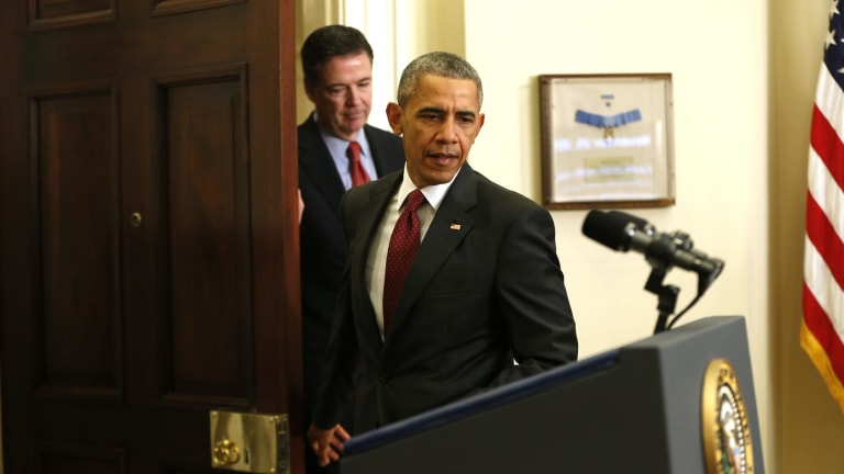 President Barack Obama, followed by FBI Director James Comey, arrives in the Roosevelt Room of the White House in 2015.