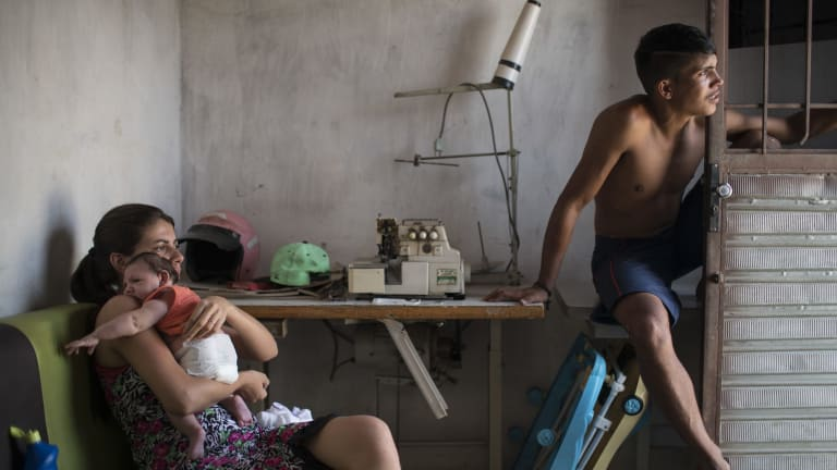 Angelica Pereira, left, holds her daughter Luiza near her husband Dejailson Arruda at their home in Santa Cruz do Capibaribe, Pernambuco, Brazil. Luiza was born in October with the rare condition microcephaly.