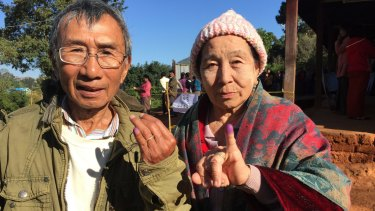 Voters in Kalaw, Myanmar, display their inked fingers after voting in the national election.