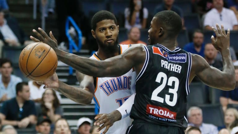 Far from overawed: Oklahoma City Thunder forward Paul George has to pass around Melbourne United forward Casey Prather.