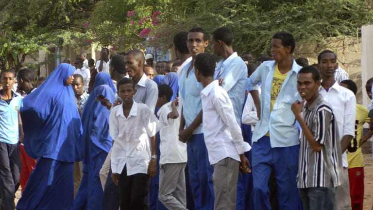 Students gather and watch from a distance outside the Garissa University College after an attack by Islamist gunmen.
