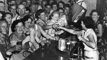 Patrons enjoy a beer at a Sydney pub in 1955.