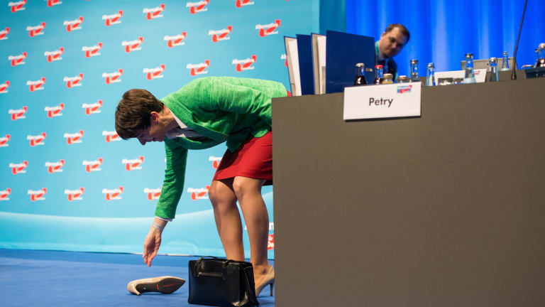 Head of the Alternative for Germany party Frauke Petry collects her shoe after stumbling during their convention.