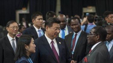 Chinese President Xi Jinping talks with Zimbabwean President Robert Mugabe in Johannesburg, South Africa, on December 5.