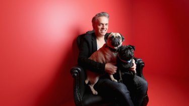 Puppy love: Craig Braybrook poses for a photo with his pugs Lola (cream) and Wilbur (black).
