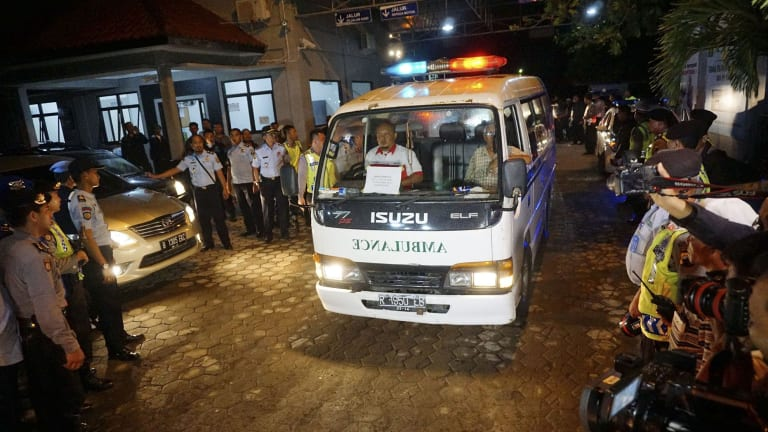 An ambulance transports the body of Nigerian prisoner Daniel Enemuo from Indonesia's Nusa Kambangan prison, where five people were killed by firing squad on Sunday.