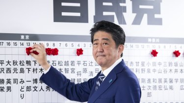 Japanese PM Shinzo Abe places a red paper rose on a LDP candidate's name to indicate a lower house election victory at the party's headquarters in Tokyo on Sunday.