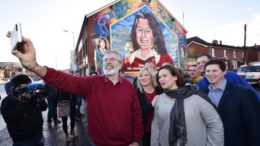 Sinn Fein president Gerry Adams takes a selfie with southern leader Mary Lou McDonald, centre, and northern leader Michelle O'Neill in Belfast.
