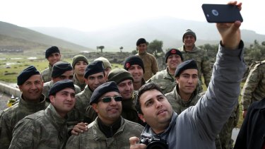A Turkish journalist takes a selfie with Turkish soldiers on the border with Syria on Monday. Operation Olive Branch on the Kurdish enclave of Afrin started on Saturday.