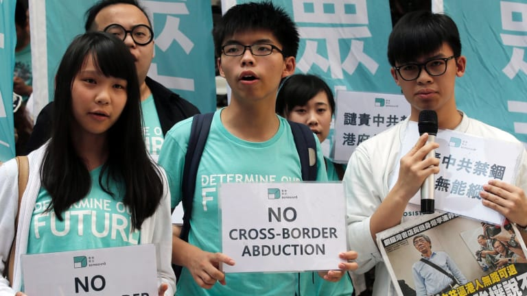 """Members of the pro-democracy group Demosisto including Joshua Wong (centre)  protest in June against the """"disappearance"""" of the Hong Kong booksellers."""