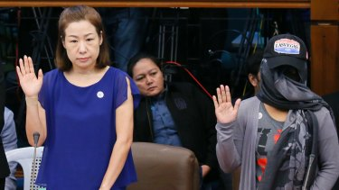Choi Kyung-jin and her former househelp Marissa Morquicho take their oaths at the start of the Philippine Senate probe into Jee Ick-joo's murder, in which police stand accused.