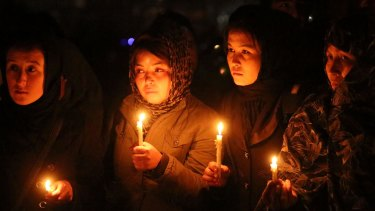 Hazara women hold candles during a memorial for beheaded Hazara victims in Kabul on Tuesday.