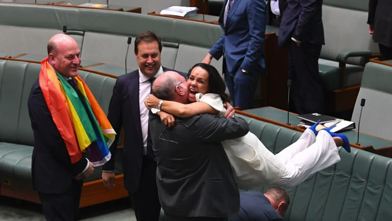 Liberal MP Warren Entsch lifts Labor MP Linda Burney into the air after the same-sex marriage vote.