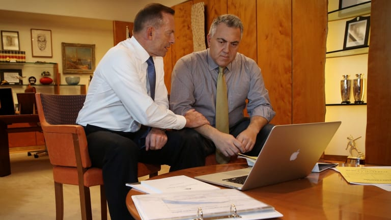 Prime Minister Tony Abbott poses with the Treasurer Joe Hockey as they look through Budget papers in Canberra on Tuesday.