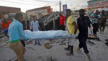 Somalis carry away the body of a civilian killed in a car bomb attack in Mogadishu on Thursday.