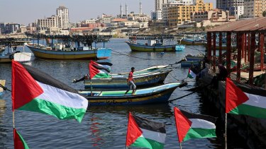 A Palestinian walks on a boat decorated with national flags as he awaits the arrival of the 13 pro-Palestinian female activists.