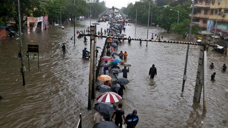 People walk through a waterlogged street following heavy rains in Mumbai, India, on Tuesday.