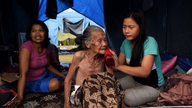 Ketut Setiari, right, bathes her 115-year-old great grandmother Nengah Brata in a tent at an evacuation camp in Klungkung, Bali.