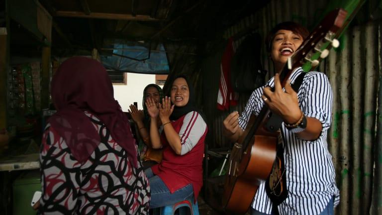 Titi Juwariyah, right, performs in a small streetside restaurant in Jakarta.